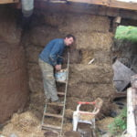 Applying slip (a chocolatey blend of clay soil and water) to protect the bales from the weather and for the cob plaster to stick to. The bale wall took one person a very wet weekend to build from start to finish.